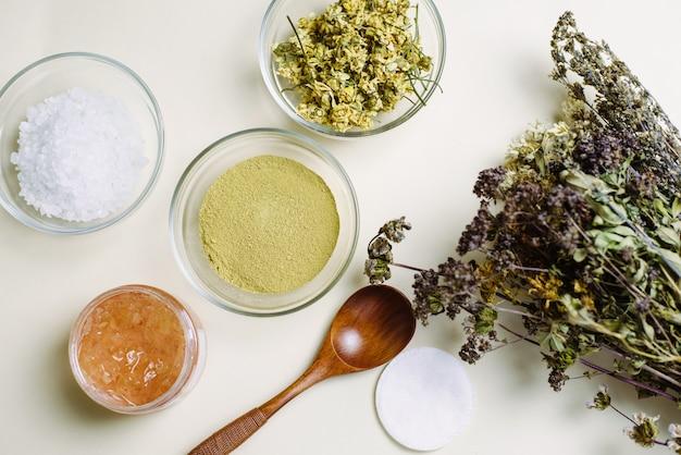 Un bouquet di fiori secchi, un cucchiaio di legno e ciotole di vetro con prodotti naturali per mescolare e creare maschere e creme naturali