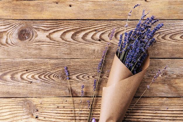 Bouquet di lavanda essiccata in carta kraft su sfondo di legno vista dall'alto spazio libero per il testo