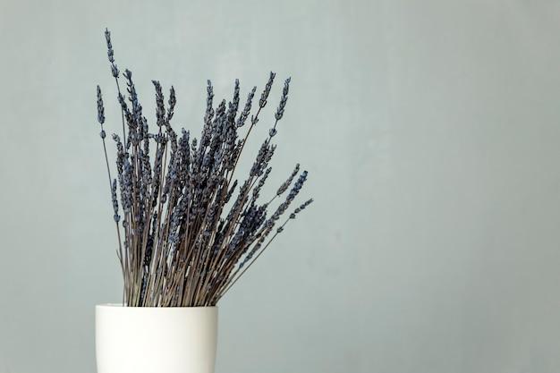 Un bouquet di lavanda blu secca si trova in un vaso bianco su un tavolo contro un muro grigio. spazio per il testo.