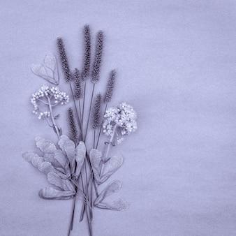 Mazzo di piante da campo secco su sfondo viola con spazio di copia