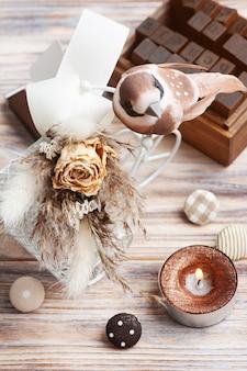 Bouquet di fiori secchi sulla bici decorativa con uccellino marrone e candela accesa sul tavolo. biglietto di auguri per matrimonio o vacanza in toni naturali