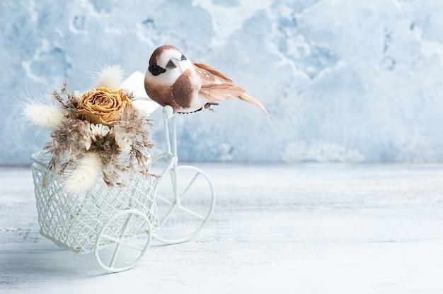 Bouquet di fiori secchi sulla bici decorativa con un piccolo uccello marrone sul tavolo. biglietto di auguri per matrimoni o vacanze in toni naturali con copia, spazio