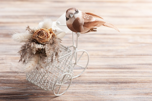 Bouquet di fiori secchi sulla bici decorativa con uccellino marrone con spazio di copia. biglietto di auguri per matrimonio o vacanza in toni naturali