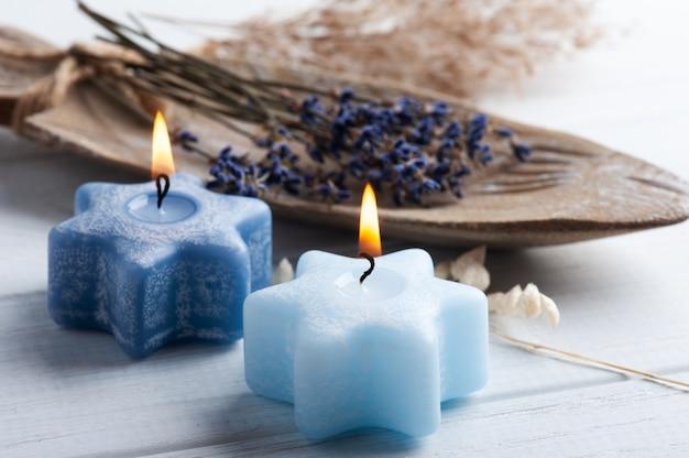 Bouquet di fiori di lavanda viola secchi disposti sul piatto rustico con candele a stella accese sul tavolo