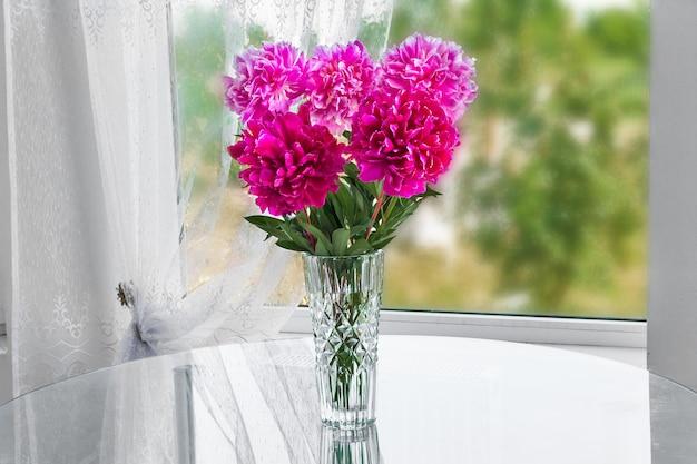 Un mazzo di cinque peonie di fiori rosa in piedi nella stanza sul tavolo in un vaso di cristallo vicino alla finestra