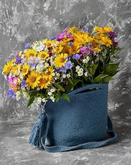 Un mazzo di fiori in una borsa borsa estiva blu giallo rosa