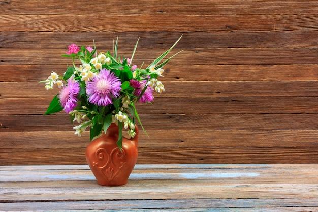 Bouquet di fiori di trifoglio, fiordalisi e gelsomino in una brocca di terracotta su un tavolo di legno