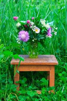 Un bouquet di fiori di trifoglio, fiordalisi e gelsomino in un vaso di vetro su un vecchio sgabello in legno