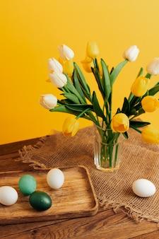 Bouquet di fiori uova di pasqua vacanza decorazione sfondo giallo