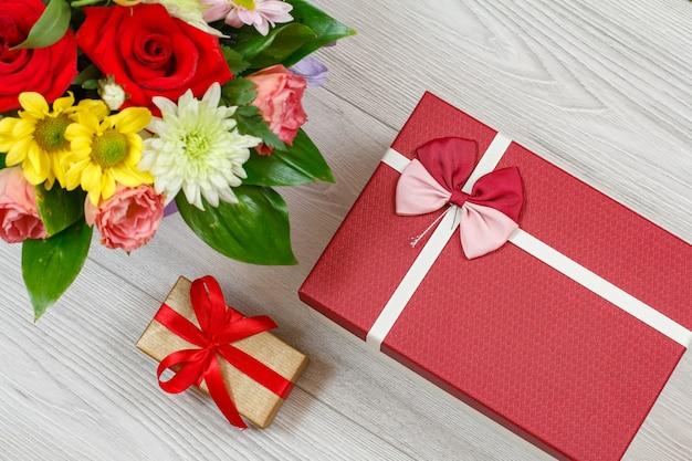 Mazzo di fiori e scatole regalo sulle tavole di legno grigie. vista dall'alto.
