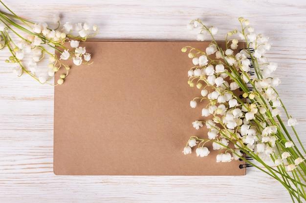 Bouquet di fiori di mughetto e quaderno di carta vuoto sul tavolo rustico in legno bianco dall'alto, vista dall'alto, spazio per testo, piatto laici.