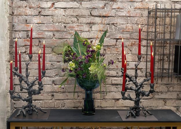 Mazzo di fiori in vaso e due candelieri di design con candele accese in interni eleganti