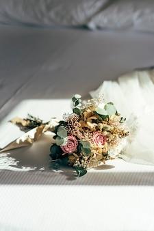 Bouquet di fiori su un letto bianco.