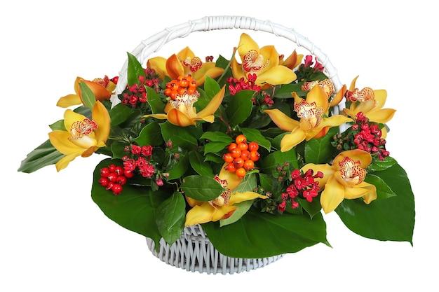 Mazzo di fiori in un cesto di vimini bianco: orchidea - grandi fiori color crema, pyracantha, hypericum. l'immagine isolata su uno sfondo bianco.