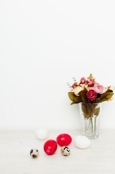 Bouquet di fiori profumati e uova di pasqua su un tavolo di legno in una stanza luminosa