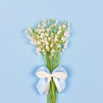 Mazzo dei fiori profumati del mughetto con un arco bianco e blu su un primo piano blu del fondo, vista superiore