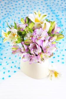 Bouquet di fresie in brocca sul primo piano tavolo
