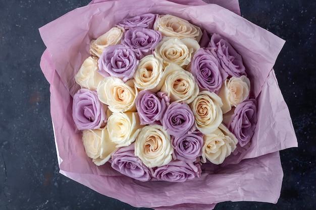Mazzo di rose bianche e viola sorprendenti fresche in carta del mestiere