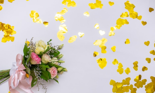 Bouquet di fiori freschi su sfondo bianco con coriandoli