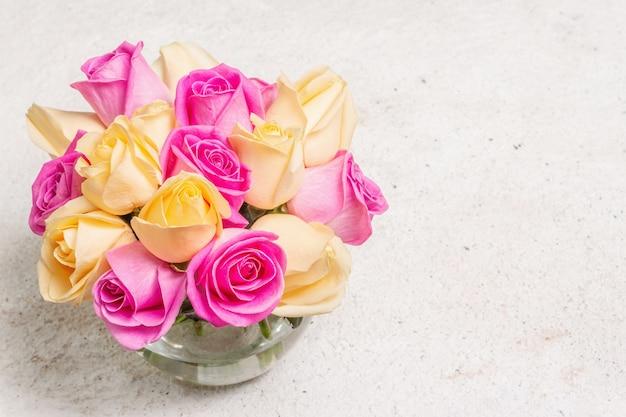 Bouquet di rose multicolori fresche in un vaso. il concetto festivo per matrimoni, compleanni, 8 marzo, festa della mamma o san valentino. biglietto di auguri, sfondo chiaro