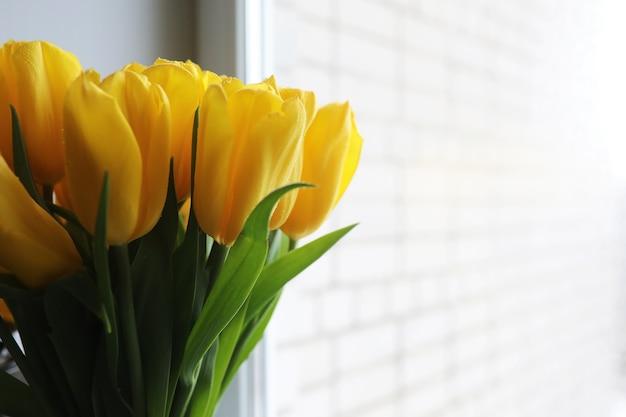 Un mazzo di tulipani gialli freschi in un vaso su un tavolo vicino alla finestra