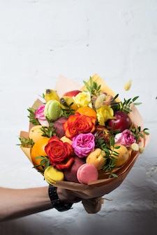 Un mazzo di frutta e fiori è dato da un uomo su uno sfondo bianco