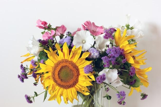 Bouquet di fiori da giardino da vicino girasole ageratum lavatera come sfondo floreale una delicata immagine estiva uno sfondo naturale