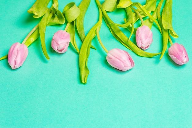 Bouquet di delicati tulipani rosa su sfondo turchese alla moda