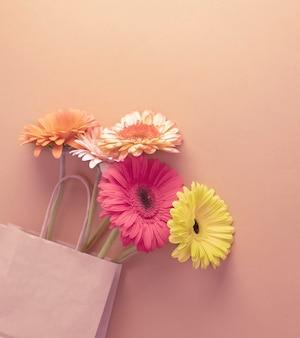 Bouquet di gerbere in una confezione artigianale sfondo di sfumature cipriate.