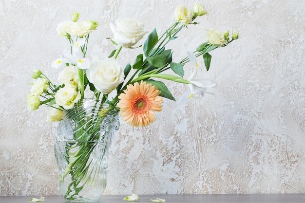 Bouquet in vaso di vetro sul tavolo nella parete di fondo