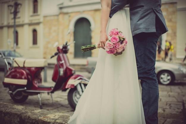 Mazzo nelle mani della sposa abbracciata dallo sposo una classica moto sfuocata