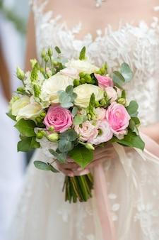 Bouquet nelle mani della sposa di rose fresche