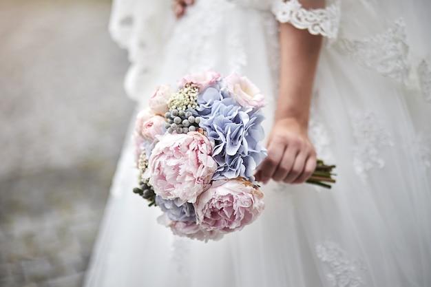 Mazzo nelle mani della sposa, donna che si prepara prima della cerimonia di matrimonio