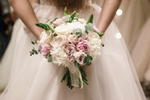 Bouquet azienda da sposa indossa abito da sposa bianco al negozio di nozze. foto senza volto