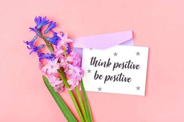 Mazzo dei fiori dei giacinti, busta lilla e carta per appunti bianca sulla tavola rosa