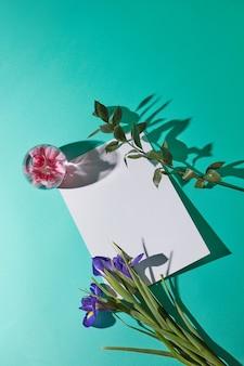Bouquet di iris su sfondo verde con vaso di vetro