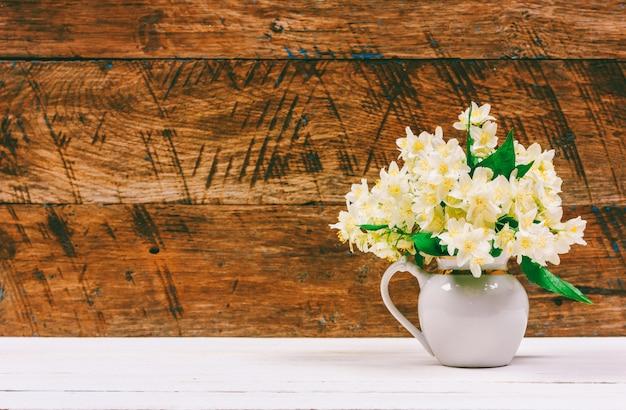 Il mazzo del gelsomino fiorisce in una brocca su una tavola bianca su un retro fondo di legno marrone con lo spazio della copia