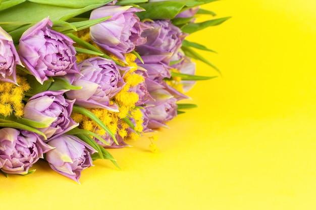 Bouquet di tulipani lilla doppia bandiera e mimose su sfondo giallo, copia spazio, vista laterale, primo piano