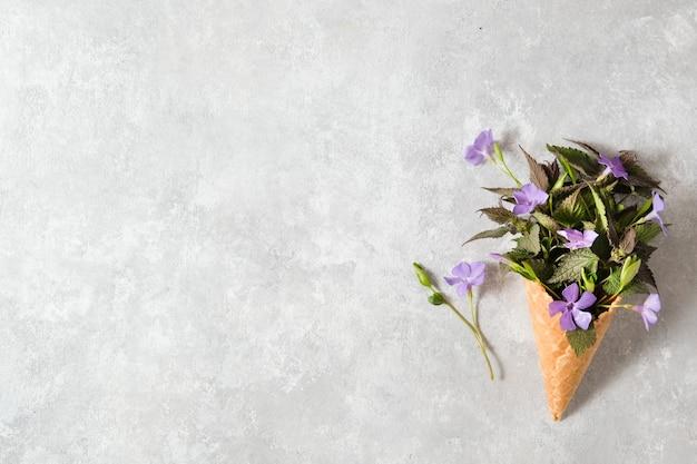 Un bouquet di fiori lilla in un cono di cialda su un tavolo grigio. concetto di primavera.