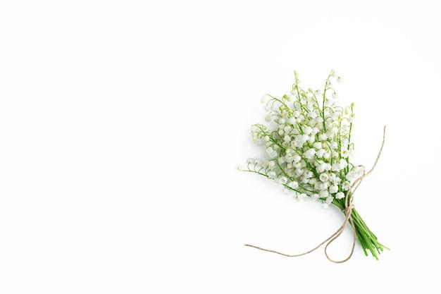 Bouquet di mughetti sul muro bianco. appartamento laico, vista dall'alto, copia dello spazio. parete floreale con fiori primaverili. stile di moda minimalista