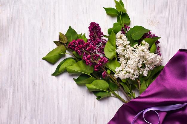 Bouquet di fiori lilla e drappeggi viola su sfondo bianco. copia spazio.