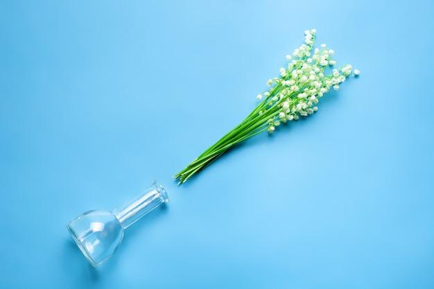 Bouquet di mughetti accanto al vaso di vetro trasparente vista dall'alto con retro isolato blu...