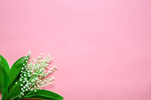 Bouquet di mughetto nell'angolo sinistro con spazio vuoto piatto con sfondo rosa