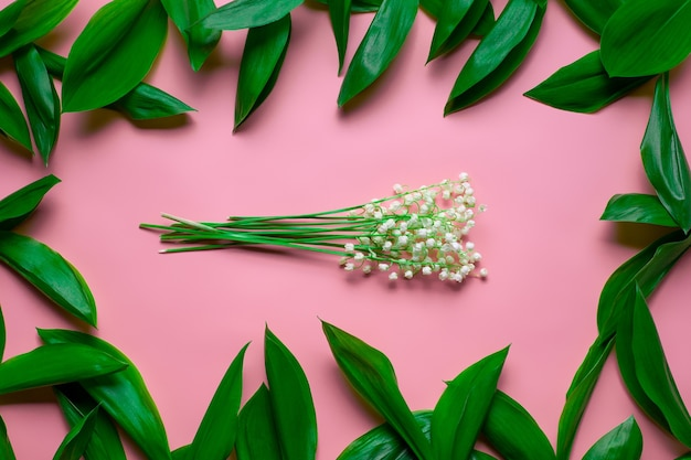 Bouquet di mughetto con foglie verdi come cornice floreale piatta con sfondo rosa