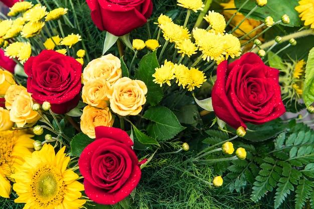 Un mazzo di rose multicolori. rose rosse e gialle in un bouquet. concentrati sulle rose di mezzo.