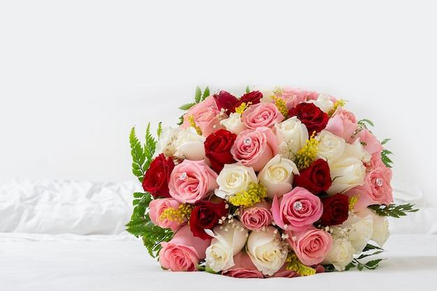 Bouquet di rose multicolori per un matrimonio su sfondo bianco