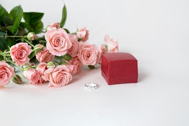 Bouquet di fiori di rosa rosa pallido e anello di fidanzamento che si trova davanti alla confezione regalo rossa
