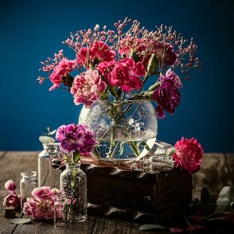 Bouquet di garofano rosa in vaso di vetro sulla superficie blu scuro. festa della mamma, biglietto di auguri di compleanno. copia spazio