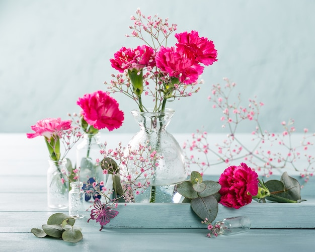 Bouquet di garofano rosa in vaso di vetro sulla superficie in legno turchese chiaro. festa della mamma, biglietto di auguri di compleanno. copia spazio