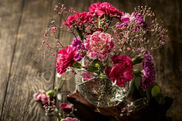 Bouquet di garofano rosa in vaso di vetro sulla vecchia superficie in legno. festa della mamma, biglietto di auguri di compleanno. copia spazio